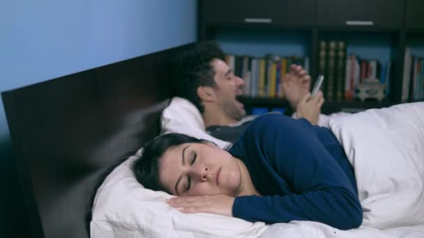 focus on Marriage, crisis, frustration.Young wife gets angry with her husband uses the smartphone in bed
