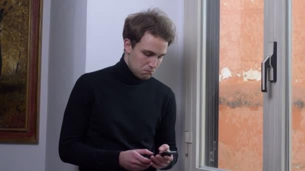 portrét dobré zprávy, štěstí, jásání. Mladý muž přijme telefonní hovor a radosti