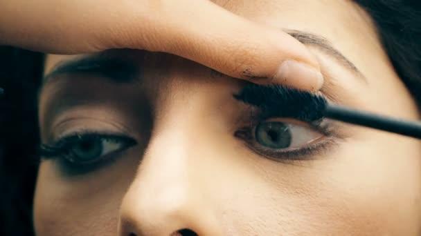 applying mascara on cute model eyes - close up