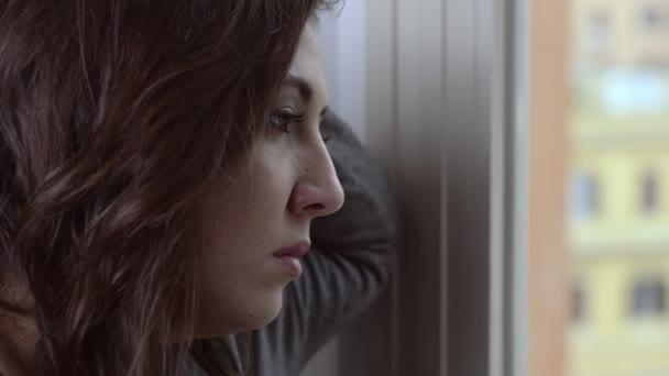 krásná žena v okně v depresi. smutek, starosti, problémy