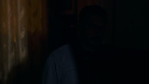 Kriminalität, Gefahr, Waffen. Mann in der Dunkelheit richtet Waffe in die Kamera