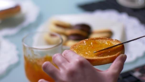 Traditionelles italienisches Frühstück. Verbreitung von Marmelade auf Zwieback mit Messer
