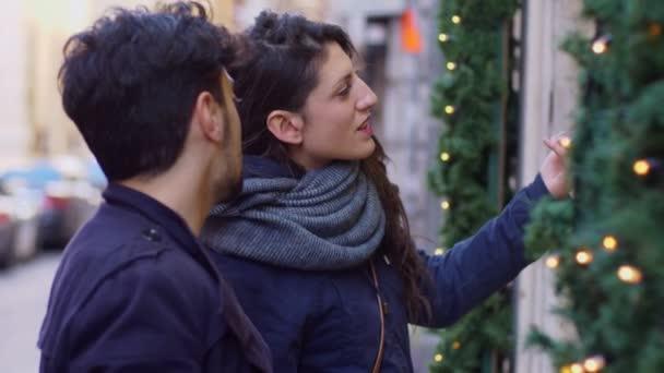 Vánoční nákupy. Mladý pár při pohledu na okna v ulici profilu
