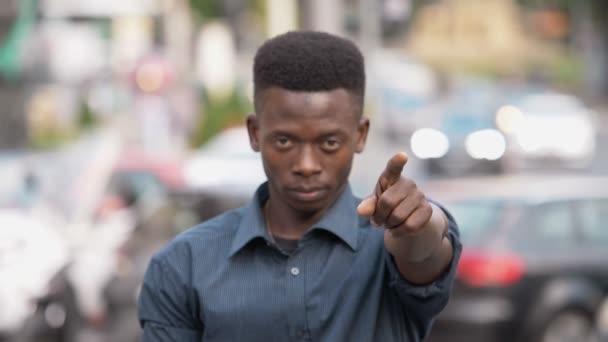 mladík vážné afroamerické body na kameru s prstem