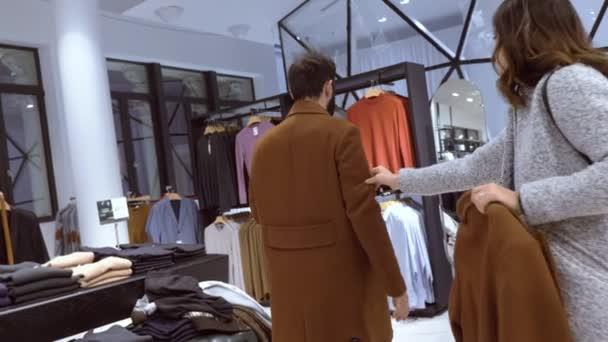 žena pomoci svým přítelem vyzkoušet kabát v oblečení store - pomalý pohyb
