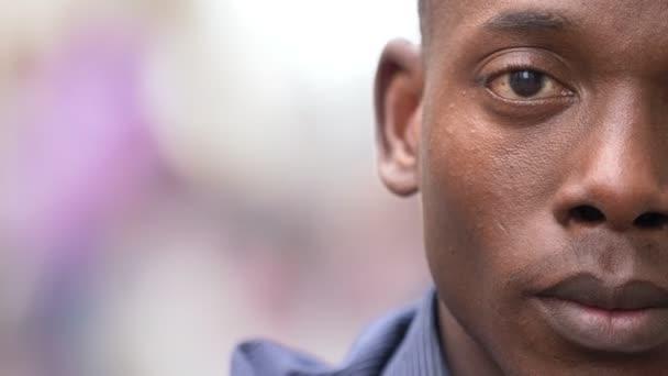 Young black african man staring at camera outdoor- half face