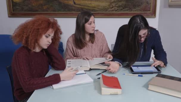 Tři studentky studium togeher knihy, zařízení, učení