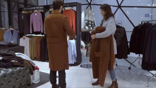 mladá žena radí nákupy manželovi v obchodě s oděvy