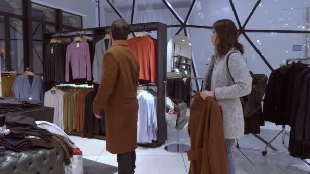 Člověk se snaží kabát pomohla jeho manželky v obchodě s oděvy