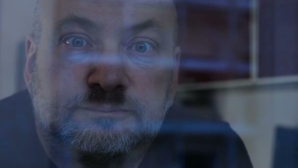 Zamyšlený snění zralý muž za sklem okna, zíral na kameru