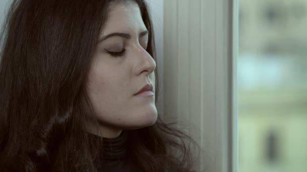 portrét osamění, deprese. smutná mladá žena při myšlení okna