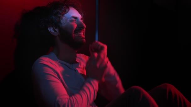 Zoufalý smutný muž sedící sám v temném pláči. Závislost, deprese