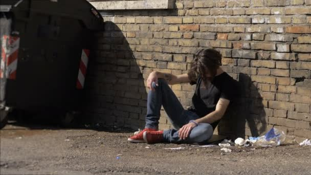 young man done drug alone sitting in the street.Drug,addiction,degradation