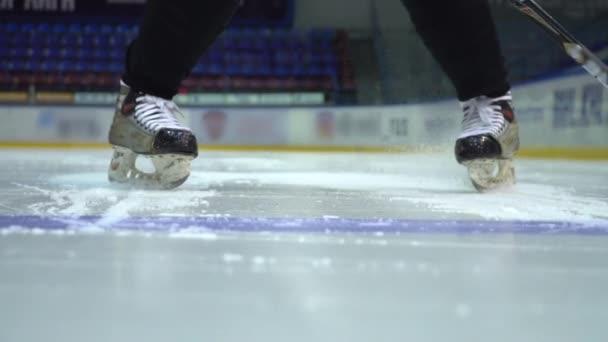 Lední hokej. Hokejový brankář se brzdění na ledě před kamerou v pomalém pohybu