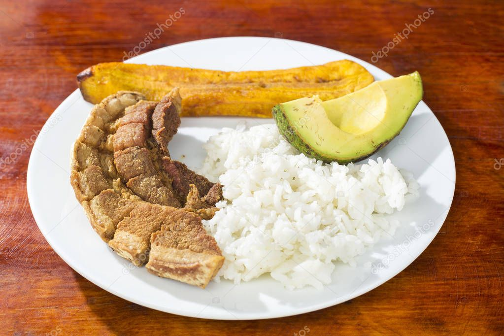 Pork rind, rice, fried banana and avocado - Typical Colombian dish