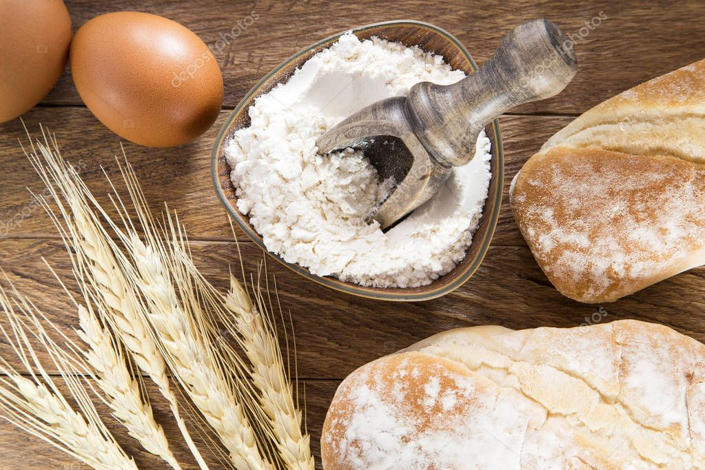 Artisan bread, flour and eggs on the wooden table