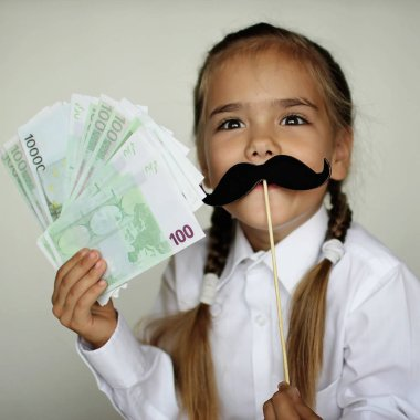 A cute little girl holding a fake felt moustache in a stick in front of her face and paper money in her hand over white background, happy father day and men health concept