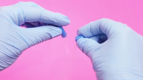 Hands in blue medical gloves open a drug capsule.