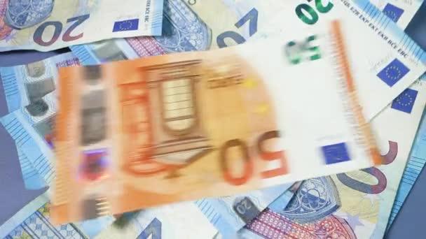 Euro bankovky spadají na stůl.
