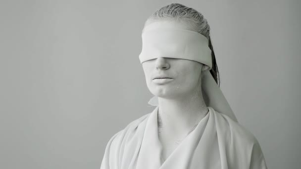 close-up portrait of a living statue. the goddess of justice is Themis with a blindfold. the statue comes to life