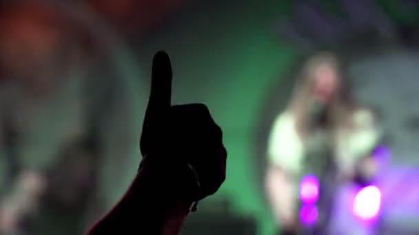 Esti Rock koncert. Emberek Cheer mozog a Lift, és tapsolnak ellen a Strobing rivaldafény kórusban. a kéz közelről felfelé irányul, és a rock and roll jel mutatja. villognak a fény