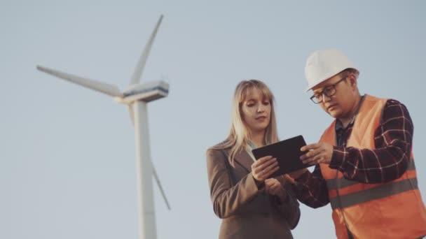Obchodní lady a mladý muž v přilbu a reflexní vestu na pozadí větrných mlýnů vytvořit stavební projekt. Podnikatel a dodavatelem při výstavbě zařízení