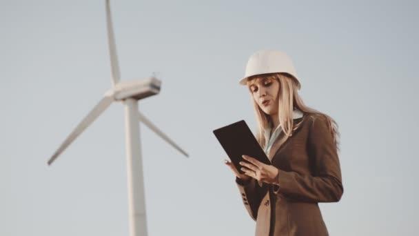 Výstavba obchodních a mladých lidí. Obchodní žena v reflexní vestu a helmu funguje v digitálním tabletu na pozadí objektu ve výstavbě. Větrné mlýny na pozadí.