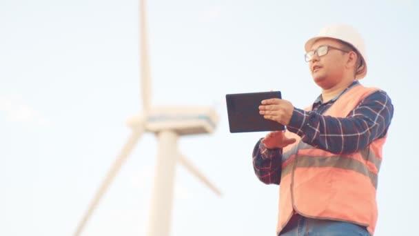 Výstavba obchodních a mladých lidí. Dodavatel v reflexní vestu a helmu děl v digitálním tabletu na pozadí větrných mlýnů. Výstavba a Správa zařízení