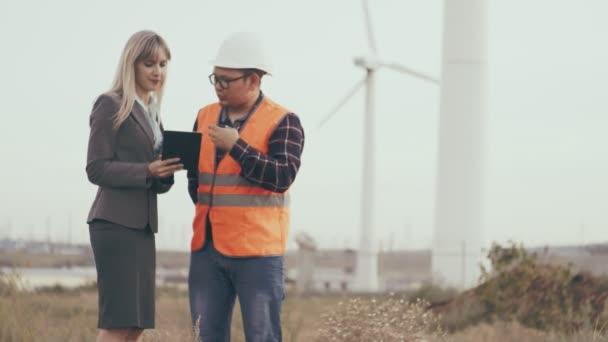 Stavební podnik. Zhotovitel v reflexní vestu a helmu pracuje s obchodní žena s digitálním tabletu na pozadí zařízení a větrných mlýnů. Výstavba nových zařízení