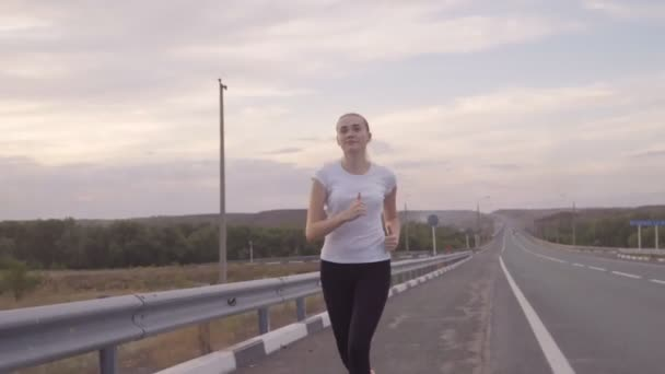 Active rest and beautiful landscape. Girl in a white t-shirt and bright sneakers running on the road at sunset, hair fluttering in the wind. On the background of the route without traffic signs are
