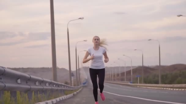A sporty girl in a white t-shirt and light sneakers runs along an empty track outside the city. Beautiful forest landscapes and sunset in the background. Active lifestyle and health care.