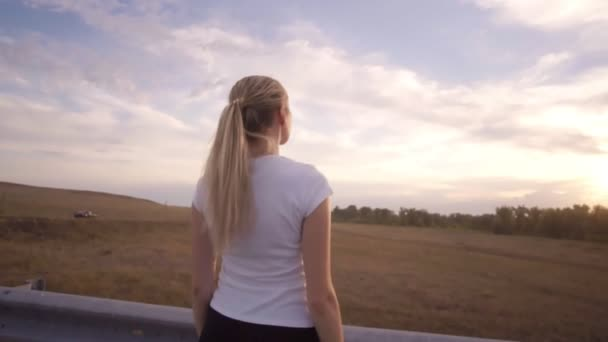 A sporty girl in a white t-shirt and with long hair does breathing exercises on an almost empty track outside the city. Athletics classes in the setting sun.