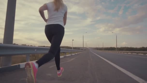 A sporty girl in a white t-shirt, in bright sneakers and with long hair runs along an empty track outside the city. Sports competitions in the country. The girl runs next to the riding car.