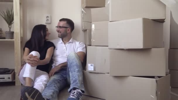 Moving young family. Husband with glasses and a white t-shirt hugs a young dark-haired wife. Couple sitting on the floor in front of shelves with things. Lots of boxes in the foreground.