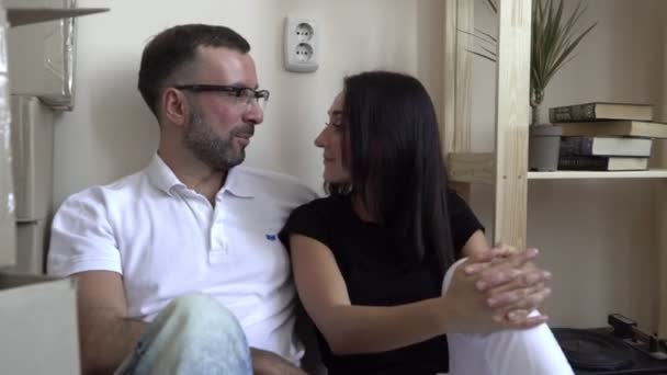 Moving a young family to a new apartment. Husband and wife sitting on the floor near the shelves and boxes of things. A man in glasses and a white t-shirt hugs his wife and smiles happily at her.