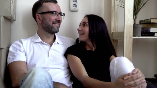 Moving a young family to a new apartment. Husband and wife sitting on the floor near the shelves and boxes of things. A man in glasses and a white t-shirt smiles joyfully at his wife. A couple in love