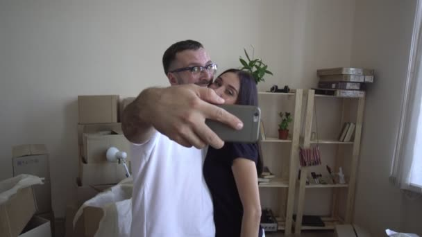Moving a young family to a new apartment. Husband and wife hug each other and take selfies on the smartphone and smile happily to each other. Man and woman are happy.