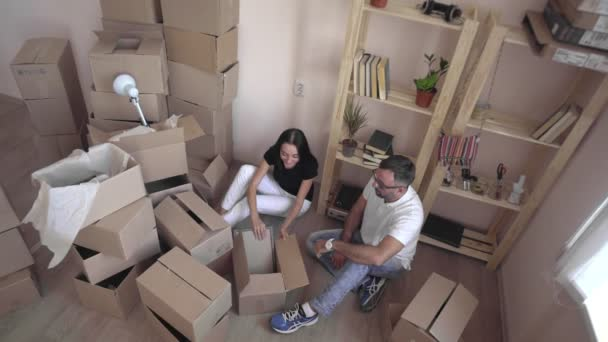 Moving a young family to a new apartment. Husband and wife hug each other and sit on the floor surrounded by boxes and things.