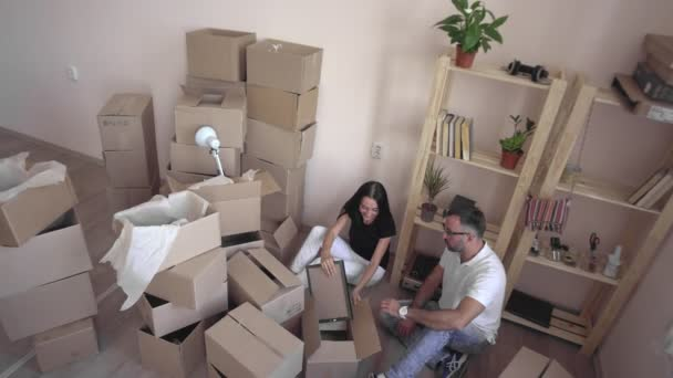 Moving a young family to a new apartment. Husband and wife hug each other and sit on the floor surrounded by boxes and things. A young couple in love is happy in a new home.