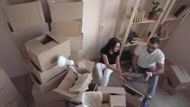 Verschieben Sie eine junge Familie in eine neue Wohnung. Mann und Frau einander umarmen und sitzen auf dem Boden, umgeben von Feldern und Dinge. Ein Junge und schöne Liebespaar bewegt sich an einem neuen Ort