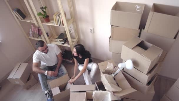Mladá rodina stěhuje do nového bytu. Muž a žena navzájem obejmout a sedět na podlaze obklopen krabic a věcí. Mladé a krásné ženy v pohledu na rodinné fotografii