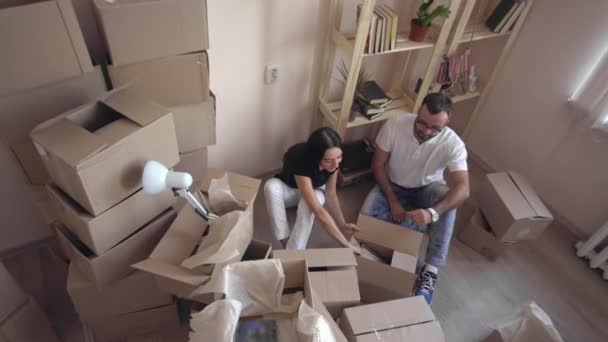 Young and beautiful couple in love looking family photo. Moving a young family to a new apartment. Husband and wife hugging and sitting on the floor surrounded by boxes.