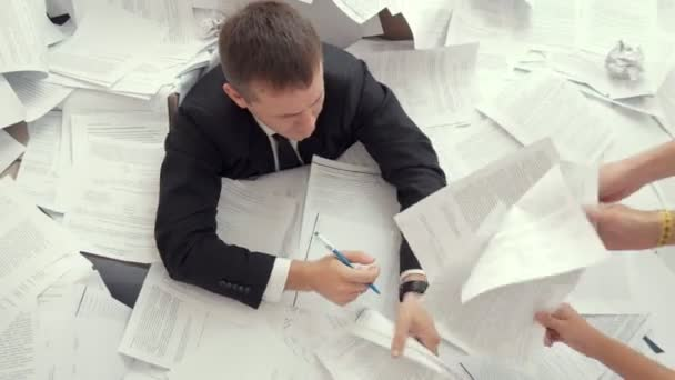 An office employee can not cope with the number of documents. A young tired man signs many documents. From all sides, hands are drawn to it with documents.