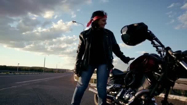 Postarší cyklista v kožené bundě a rukavice přichází na kole na pozadí prázdné silnici a na něm sedí. Žena může vidět z různých úhlů. Život postarší rocker a