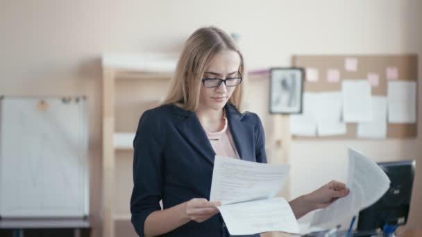 Call centrum zaměstnanec v práci v kanceláři. Mladá dívka s blond vlasy s brýlemi stojí v kanceláři, drží balíček papíru. Dívka nemůže vyrovnat s prací, nervózní a trhání papíru