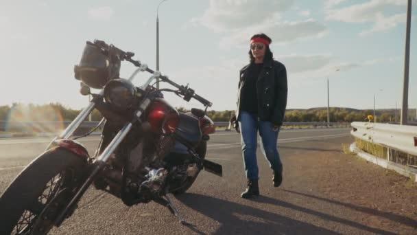 Staré motorkář a jeho motocykl. Motocykl a staré biker v pozadí přírody na prázdný dálnici. Žena ve věku odchodu do důchodu jde na motocyklu, který stojí na prázdnou stopu.