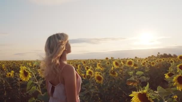 A young woman is standing in a field among sunflowers. She has blonde hair and a white dress. A woman stands with her back to the camera and looks thoughtfully at the sunset.