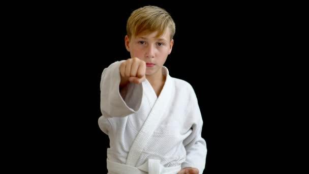 A fehér kimonó egy fiatal sportoló azt mutatja, egy lyukasztógép-val a jobb kezét. A fiú rendelkezik egy arm a derekát, és a másik halad előre. A fiú van szőke haj és sötét szemek.