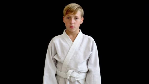A fiú van, szőke haj, és egy európai megjelenés. A fehér kimonó egy fiatal sportoló áll egy sötét háttér.