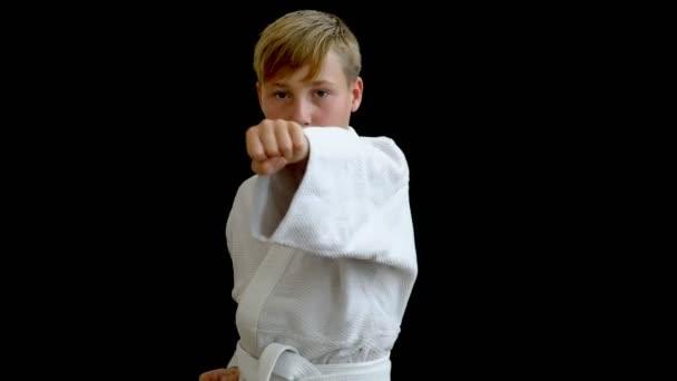 Egy fiú, egy fehér kimonó azt mutatja, hogy a sport-kick. A sportoló a sötét háttéren dob egy kar előre, és a második továbbra is a test. A kéz szinte hatálya alá tartozó, a fiúk arcát.